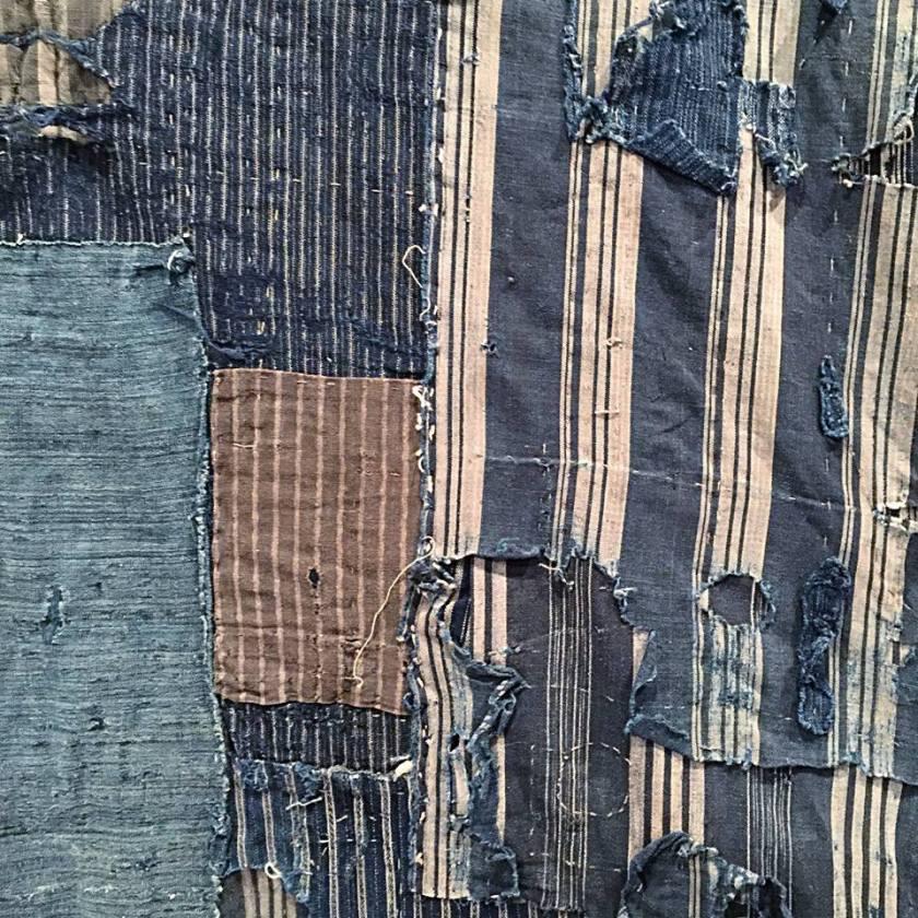 Superposition de chutes de coton indigo unis ou rayés, sur housse de futon.